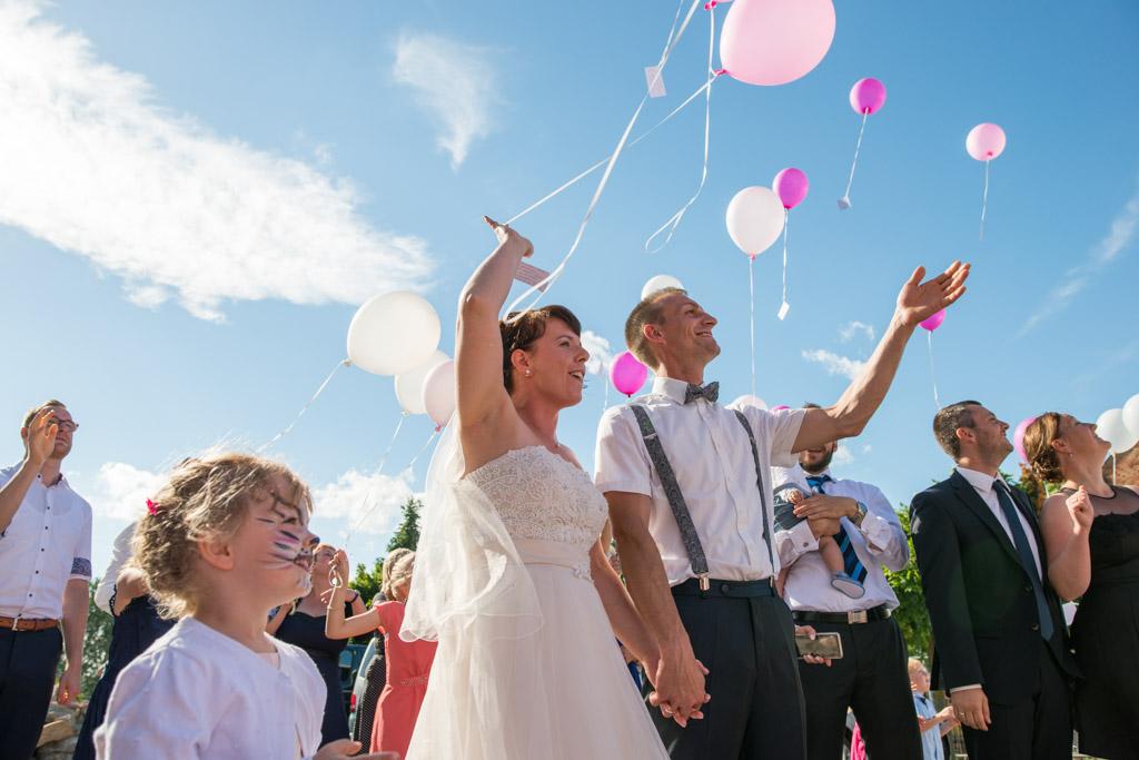 Braut und Bräutigam lassen Luftballons mit Glückwünschen der Hochzeitsgäste steigen