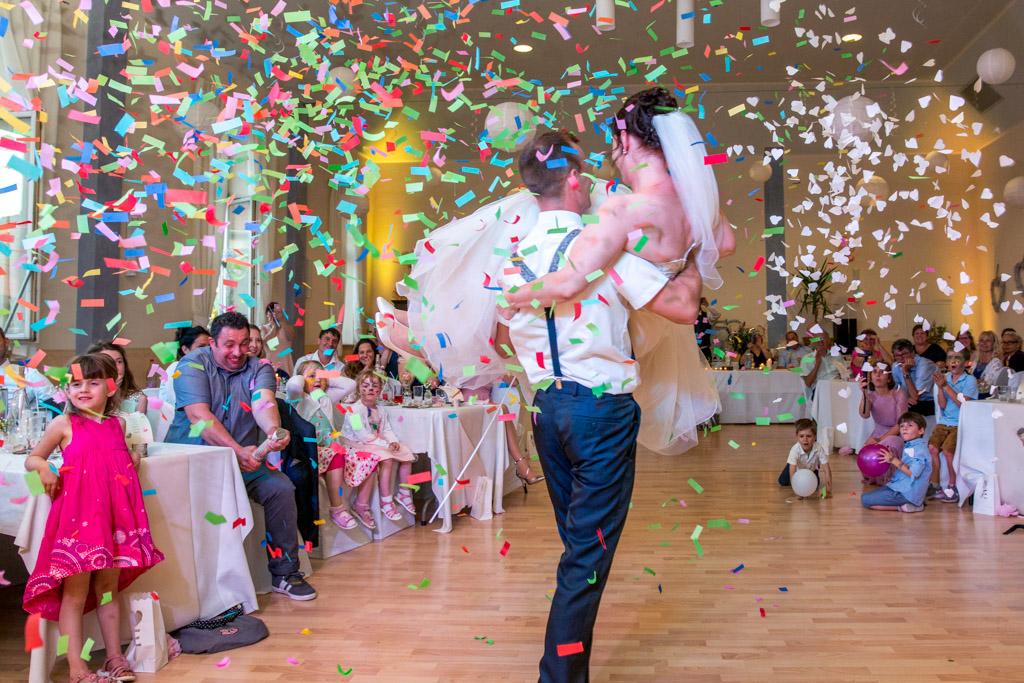 Braut und Bräutigam werden mit Konfetti während ihres Tanzes überrascht