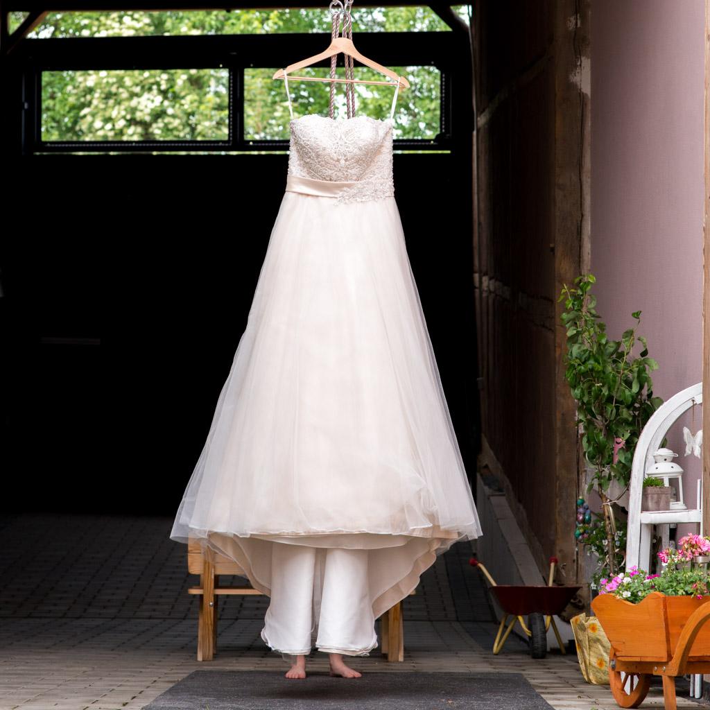 Wunderschönes Hochzeitskleid aufgehangen im Innenhof des Brautpaars