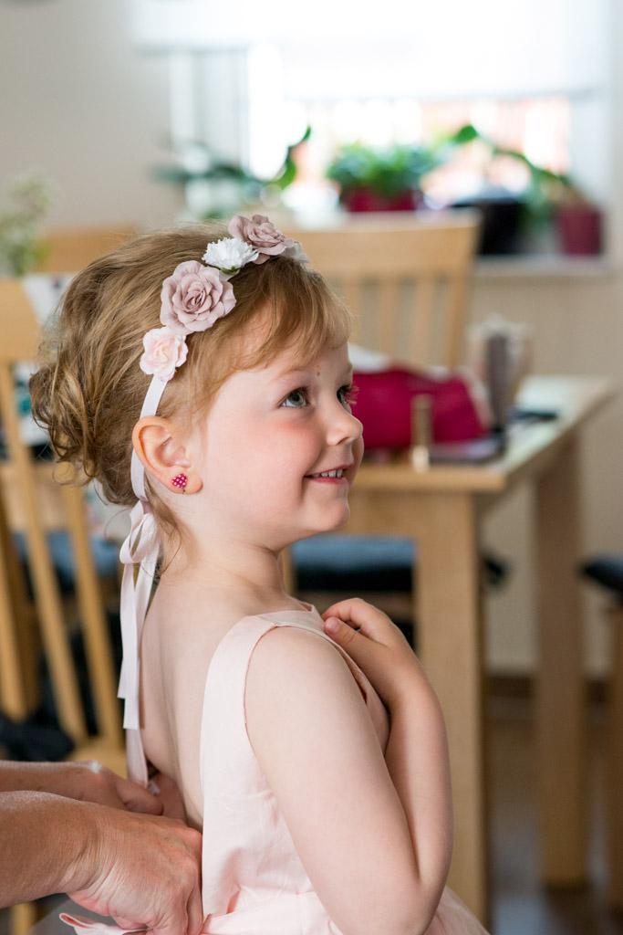 Die kleine Tochter der Braut mit Blumenhaarband