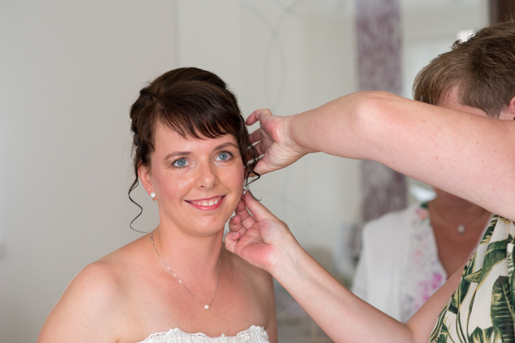 Braut mit fertigem Makeup bekommt Hilfe mit ihrem Ohrring