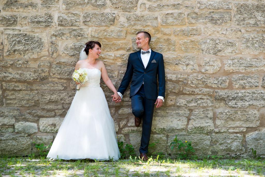 Braut und Bräutigam lachen sich an und halten Händchen