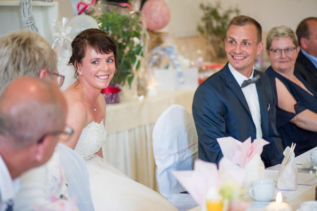 Braut und Bräutigam strahlen beide nach der Hochzeitsrede