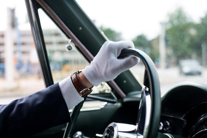 Der Chauffeur und Trauzeuge mit weißen Handschuhen am Lenkrad