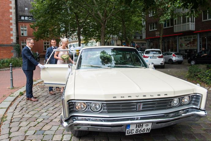 Braut steigt in das Brautauto vor dem Standesamt Hamburg-Harburg