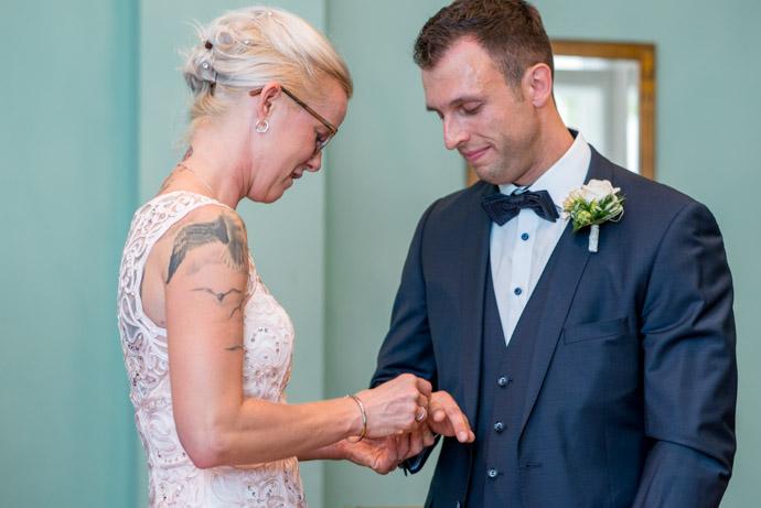 Braut steckt ihrem Ehemann den Ring an