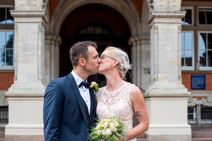 Braut und Brätigam küssen sich vor dem Rathaus Harburg