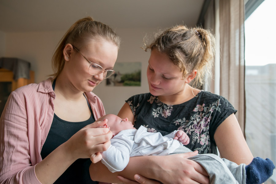 Große Schwestern mit ihrem kleinen Bruder auf dem Arm