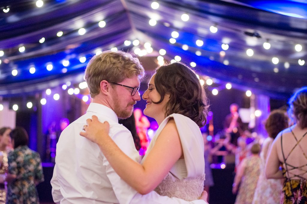 Bräutigam hält seine Braut in den Armen unter einem Himmel aus Lichtern