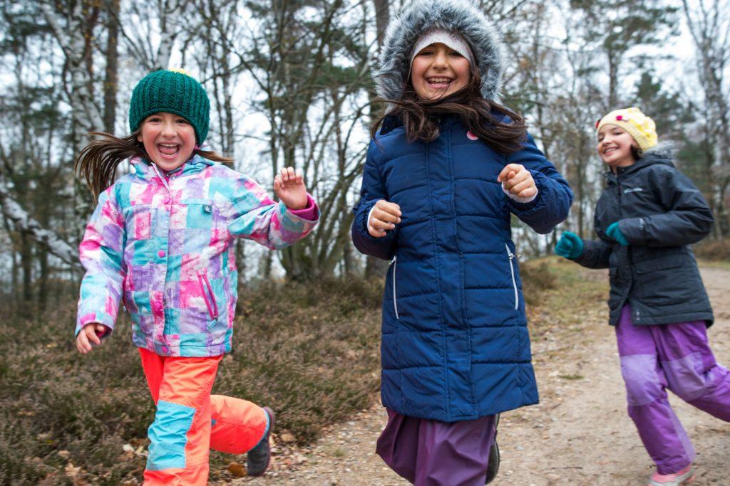 Schwestern rennen durch den Wald, lachend