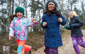Kinder in Winterkleidung rennen einen Berg herunter
