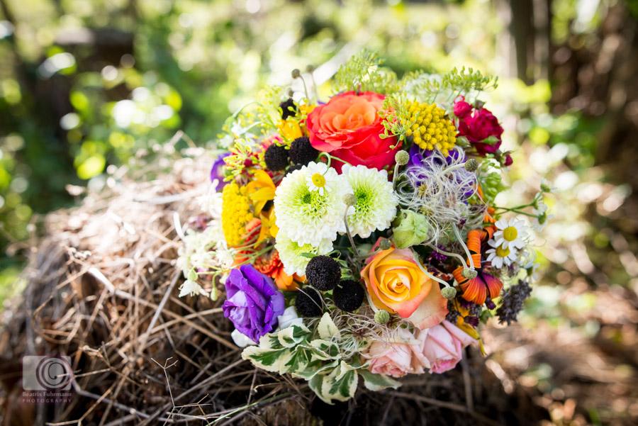 Herbstlicher Brautstrauss mit Rot, Orange, lila und gelben Blumen, gebunden von der Oma der Braut