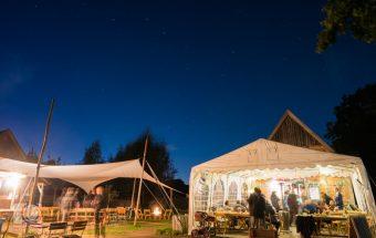 Hochzeitsfeier auf Hof Eggers - Hell erleuchtetes Zelt und Überdachung unter Sternenhimmel