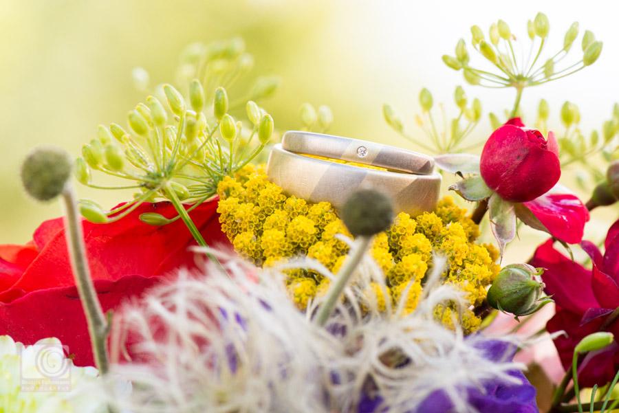 Gold und silberne Eheringe auf dem Brautstrauß