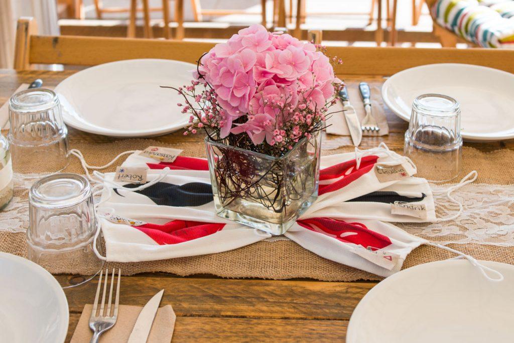 Die Gäste erhielten Mundschutze mit Schnurrbart oder Kusslippen die gleichzeitig als Tischdekoration zusammen mit pinken Hortensien funktionierten.