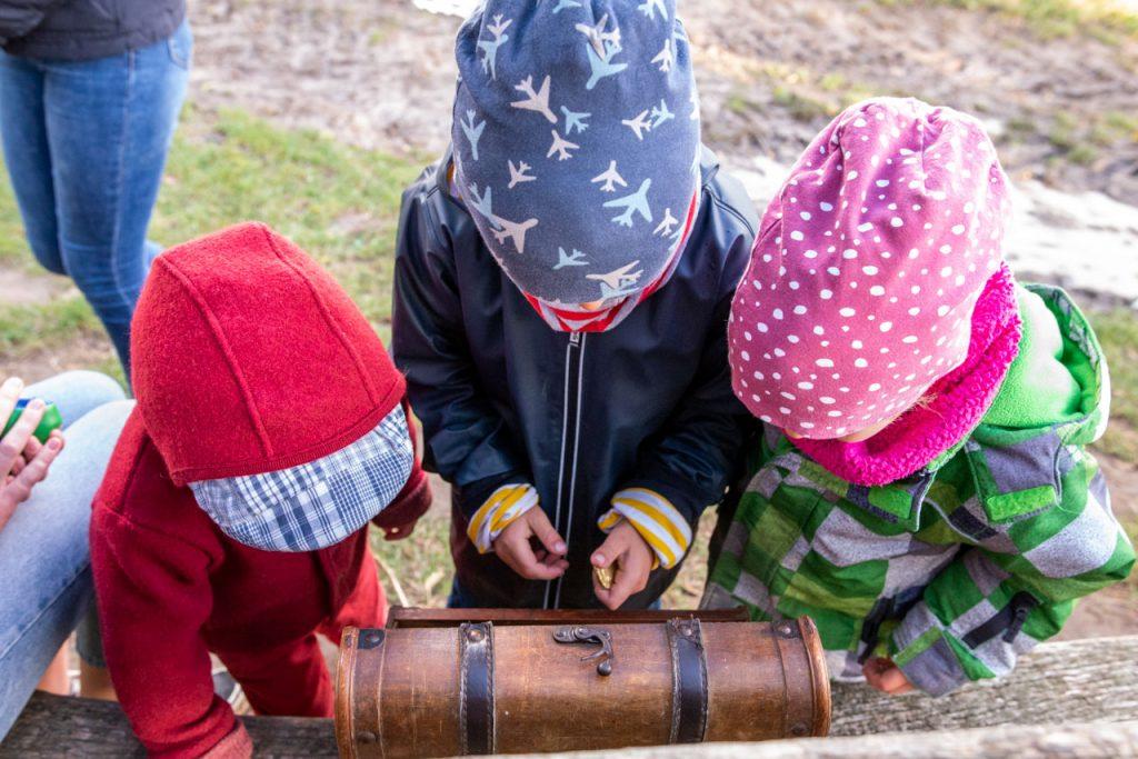 Kinder schauen in eine Schatztruhe bei der Schatzsuche auf dem Biohof Hof Eggers