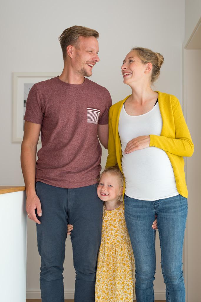 Eltern mit wachsendem Babybauch mit Tochter die zwischen beiden steht und grinst